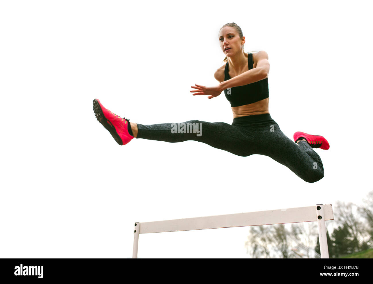 Athlete woman jumping in a running track - Stock Image