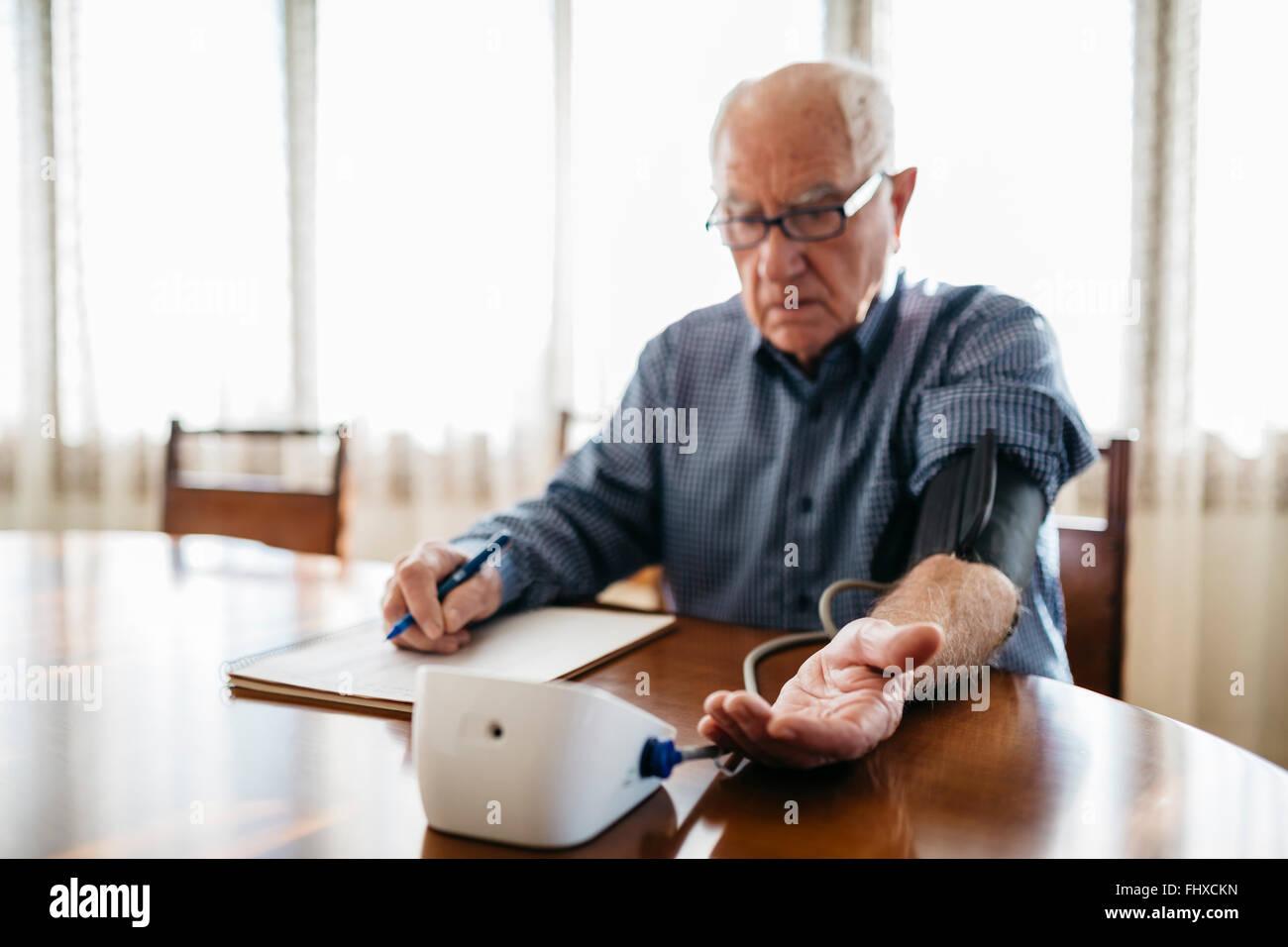 Senior man controlling his blood pressure at home - Stock Image