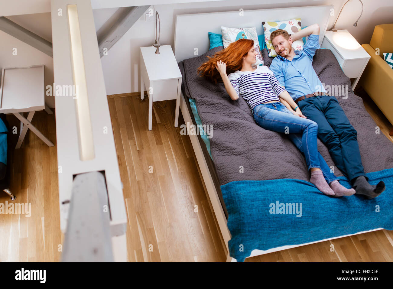 Beautiful couple resting on bed in a modern apartment - Stock Image