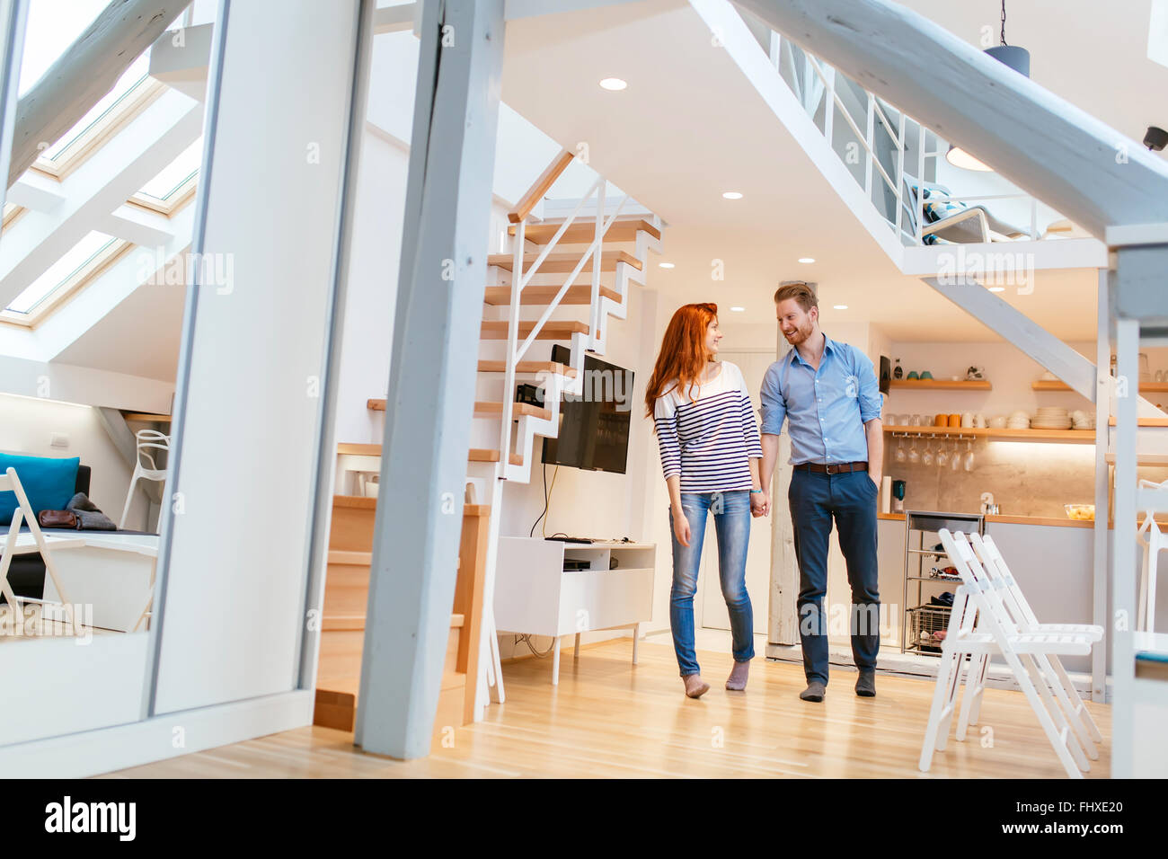 Couple moving in new apartment with smiles on their faces - Stock Image