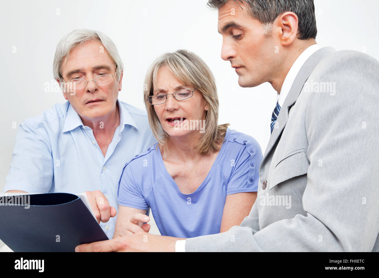 Senior couple getting financial advice from consultant at home - Stock Image
