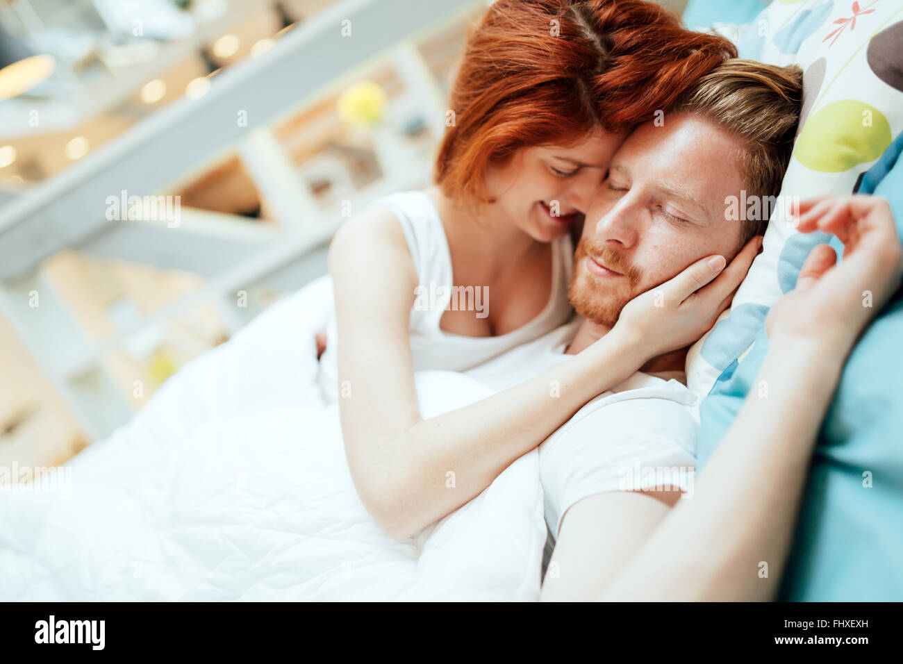 Romantic couple in love lying on bed and being passionate - Stock Image