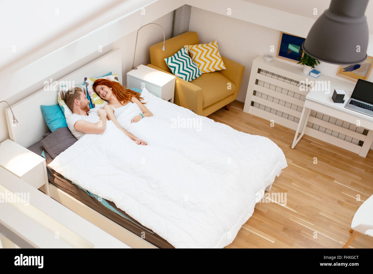 Romantic couple resting in bed and bonding during weekend - Stock Image