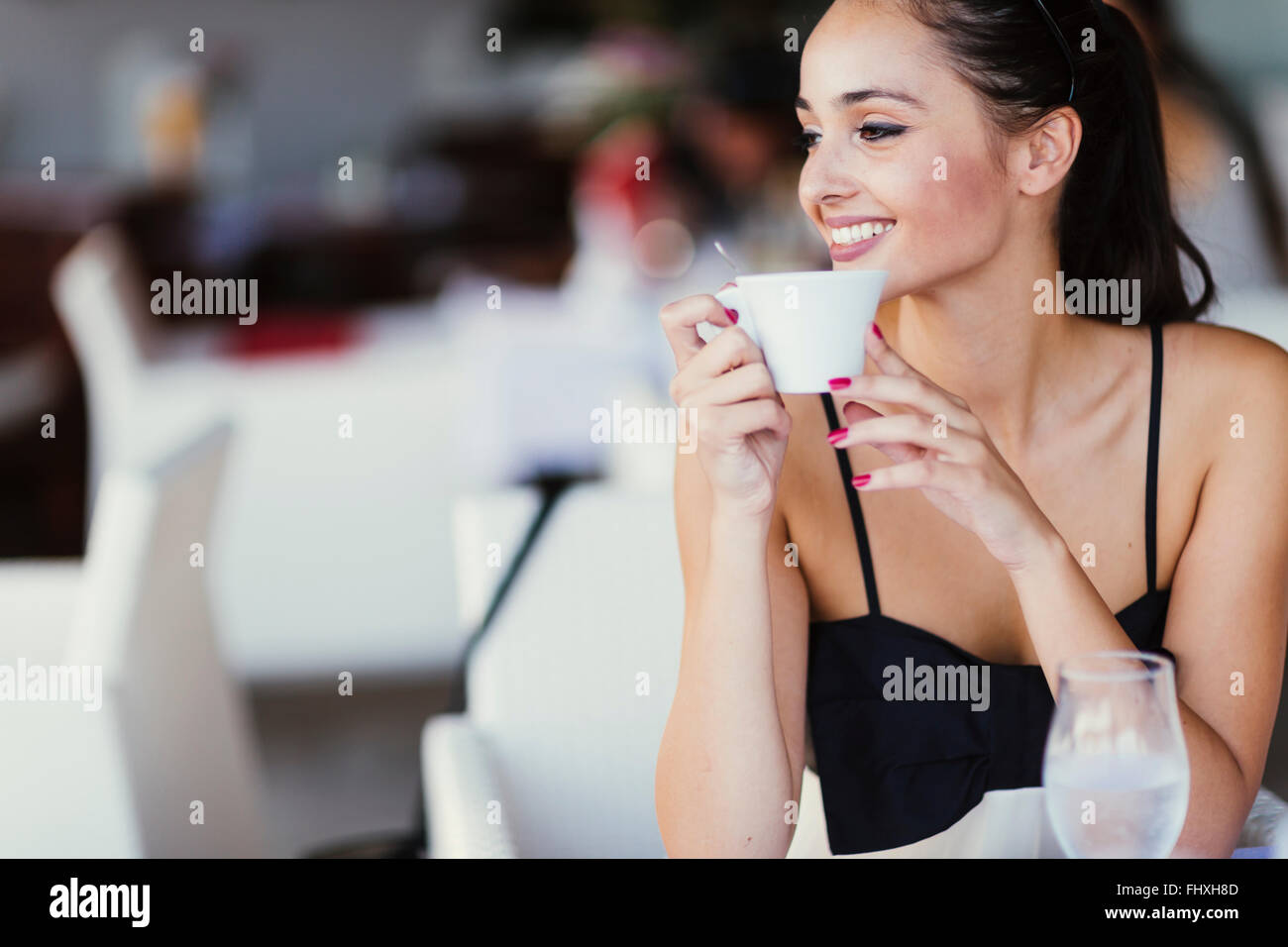 Beautiful woman drinking tea in restaurant while waiting for her meal - Stock Image