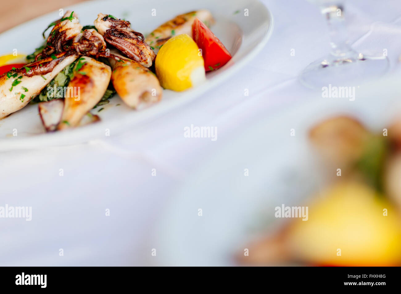 Grilled squid served on plate - Stock Image