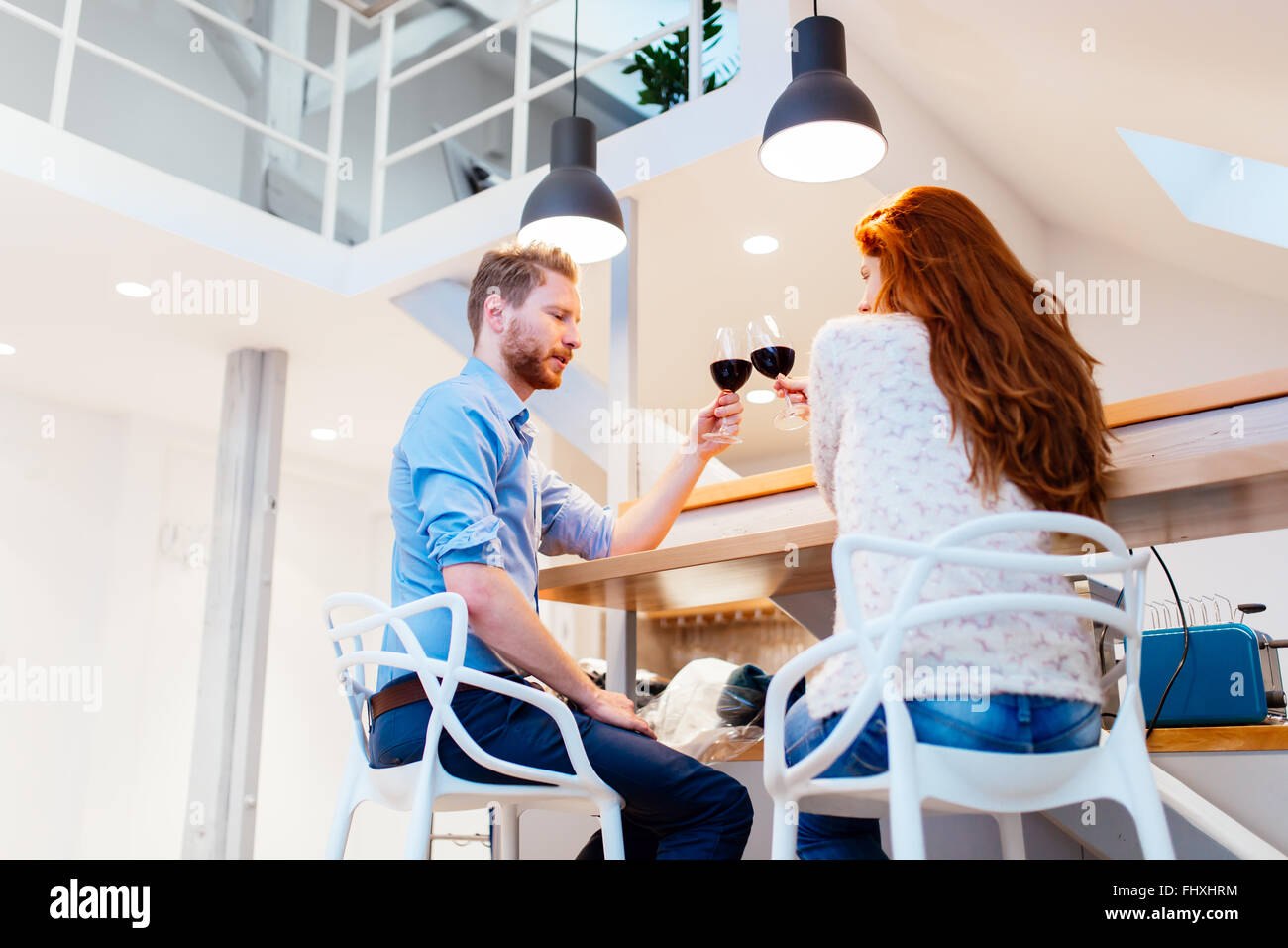 Beautiful couple celebrating moving in to new apartment by toasting wine - Stock Image