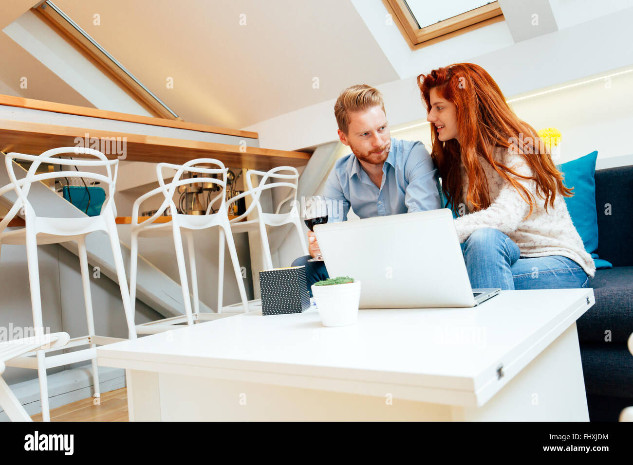 Couple surfing on internet while sitting on couch in beautiful living room - Stock Image
