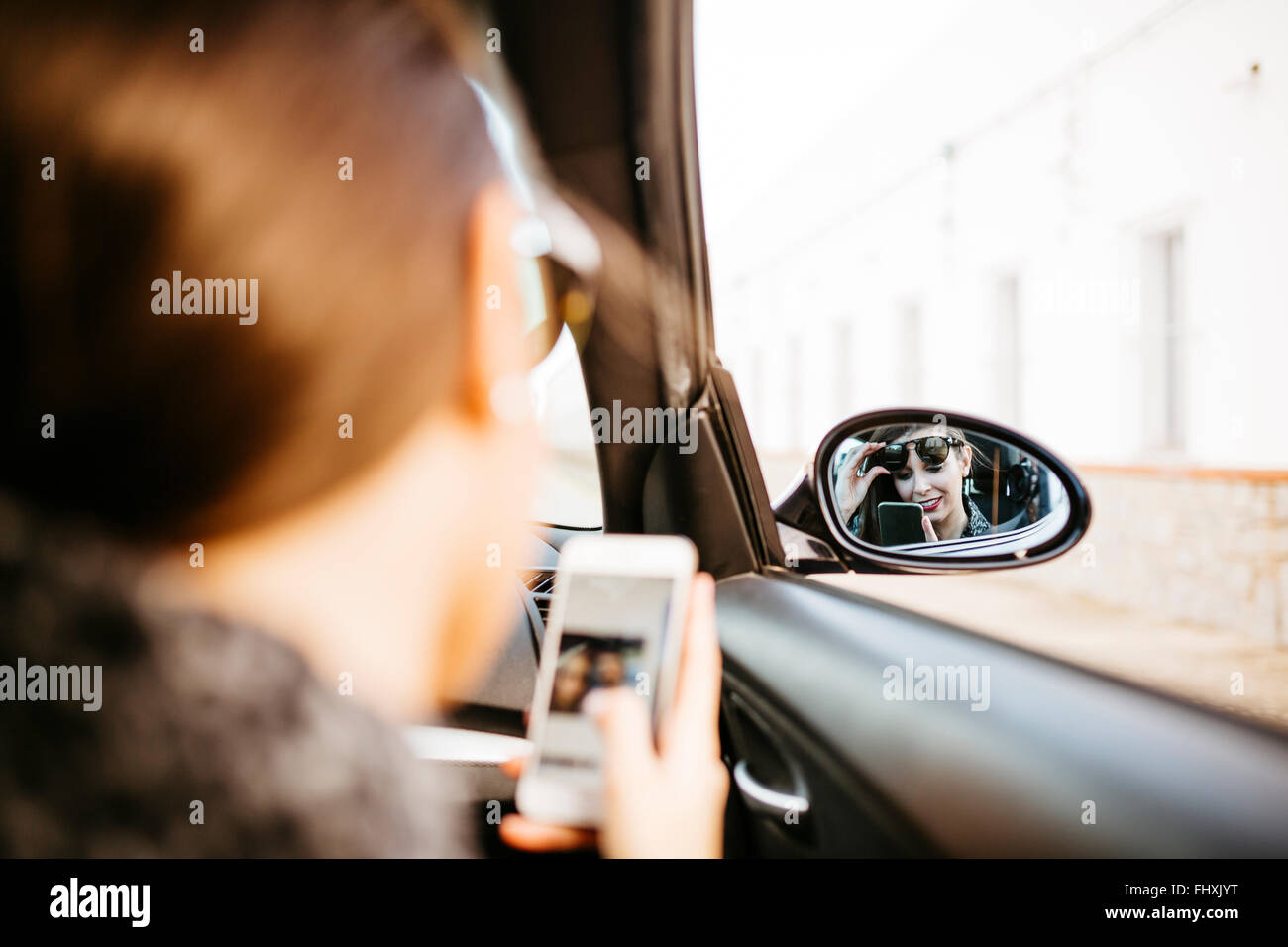 Female front passanger in car using smart phone - Stock Image