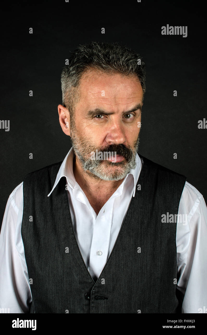 Moustached male in his 50s looking angry - Stock Image