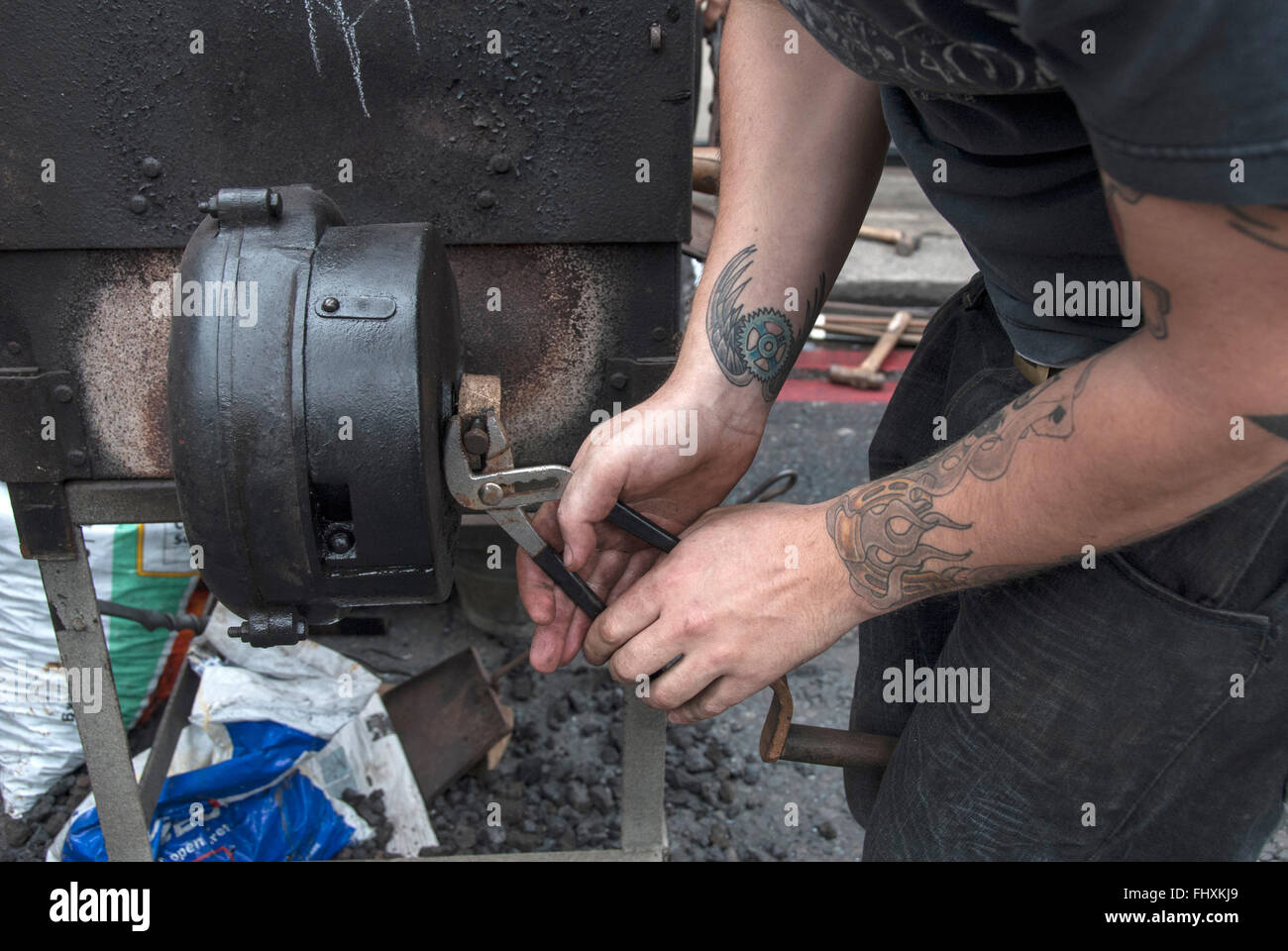 A male laborer tightens the screw on a metal devices - Stock Image