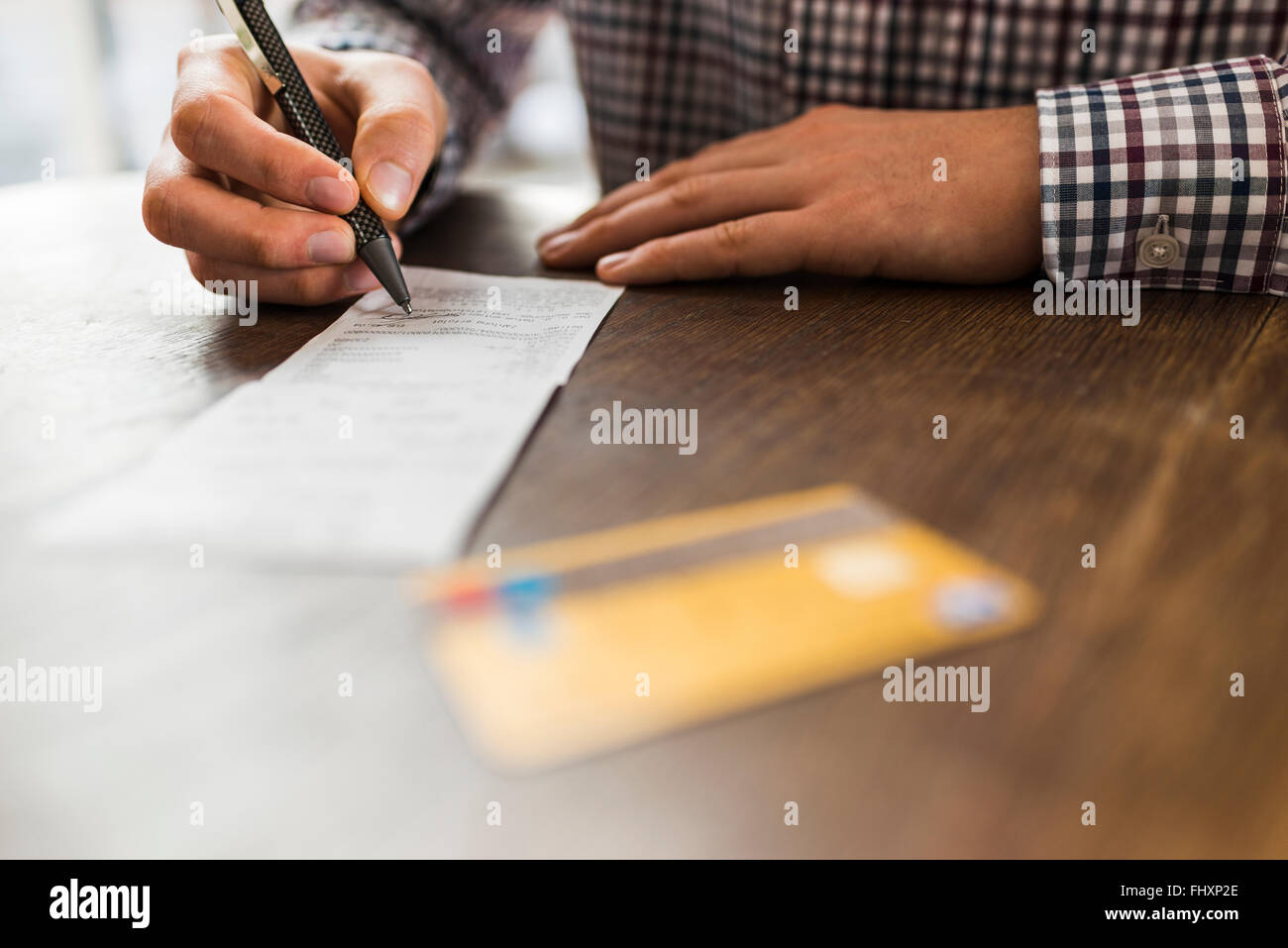 Close-up of man signing bill on table - Stock Image