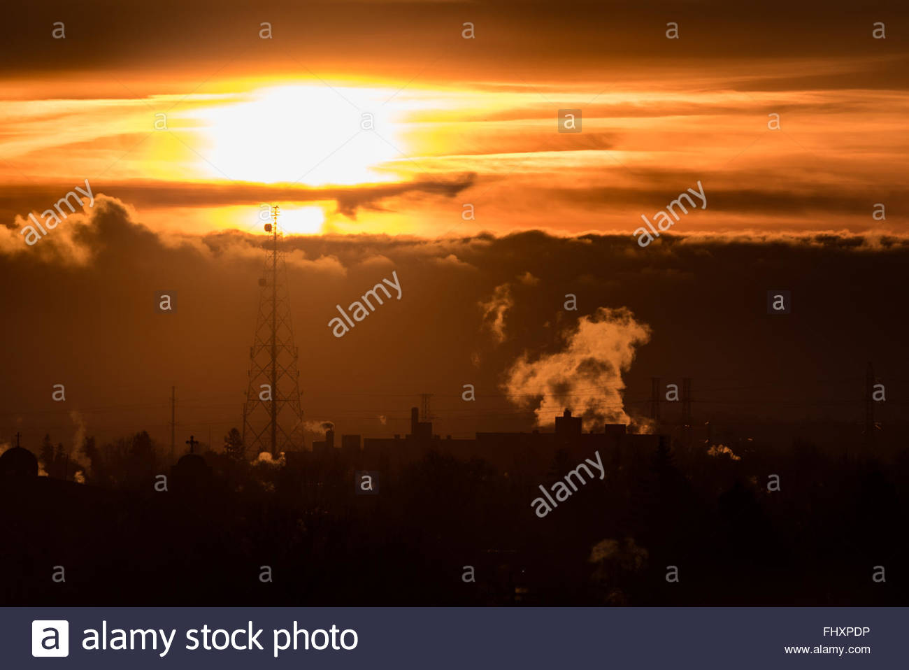 Radio or communication tower in the distance as the sun rises in the Winter morning beautifully. - Stock Image