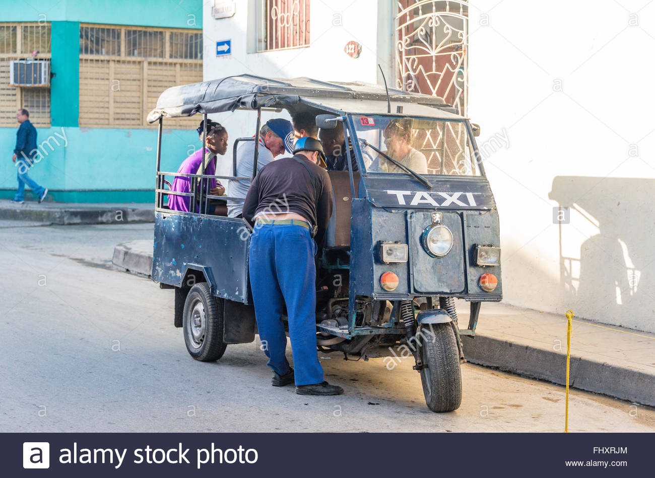 Cuban man fixing a homemade taxi. The vehicle is made from spare parts such as wheels and pistons, parts that can Stock Photo