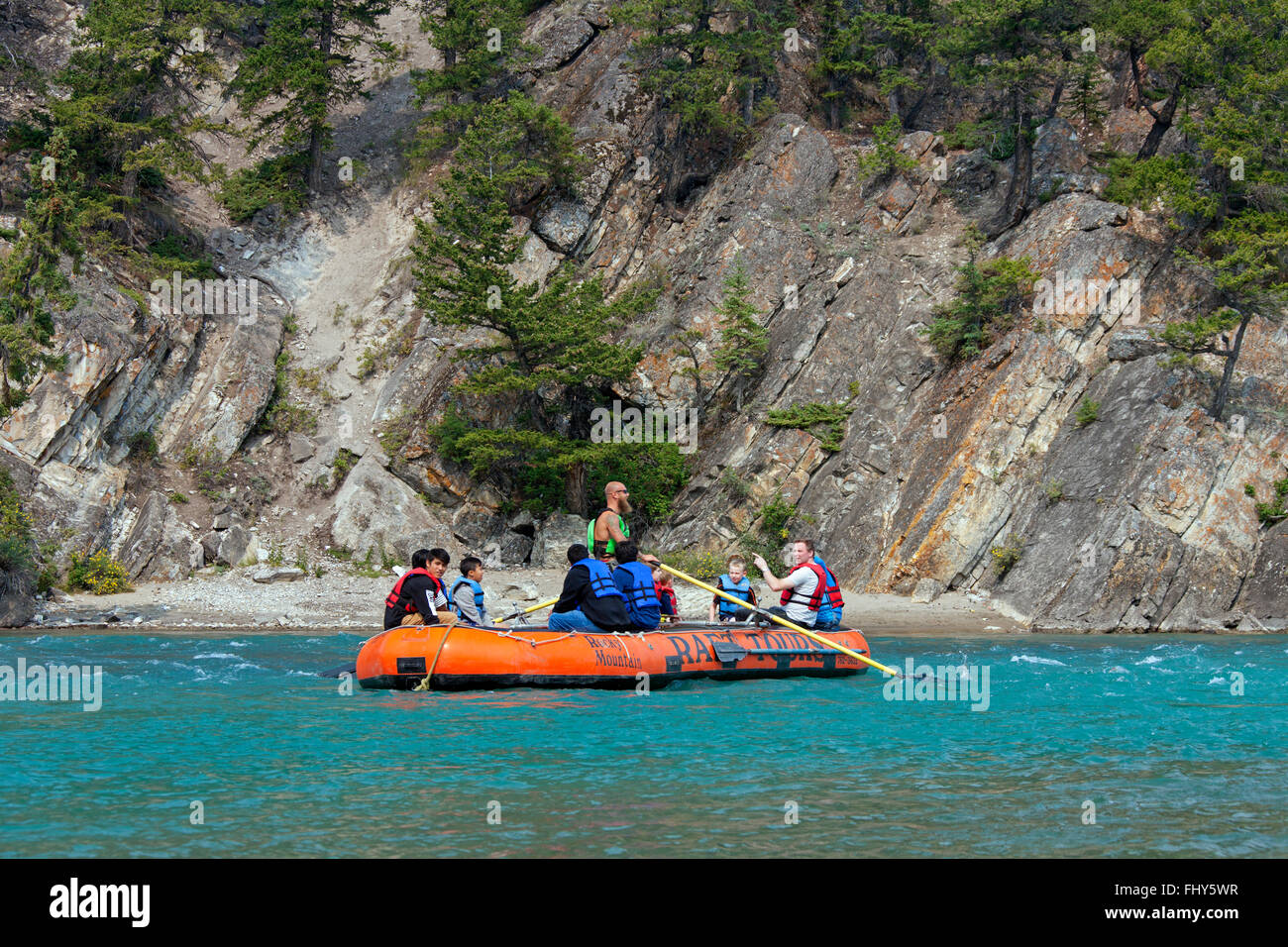 Tourists in inflatable raft rafting on the Bow River near Banff, Alberta, Canada - Stock Image