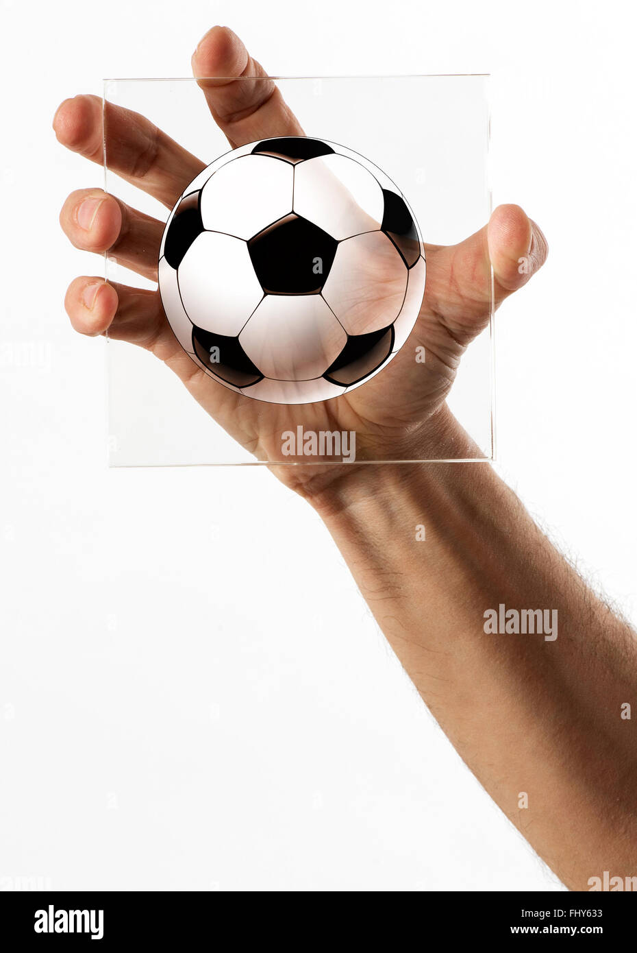 Single human hand holding a square piece of glass with a black and white soccer ball - Stock Image