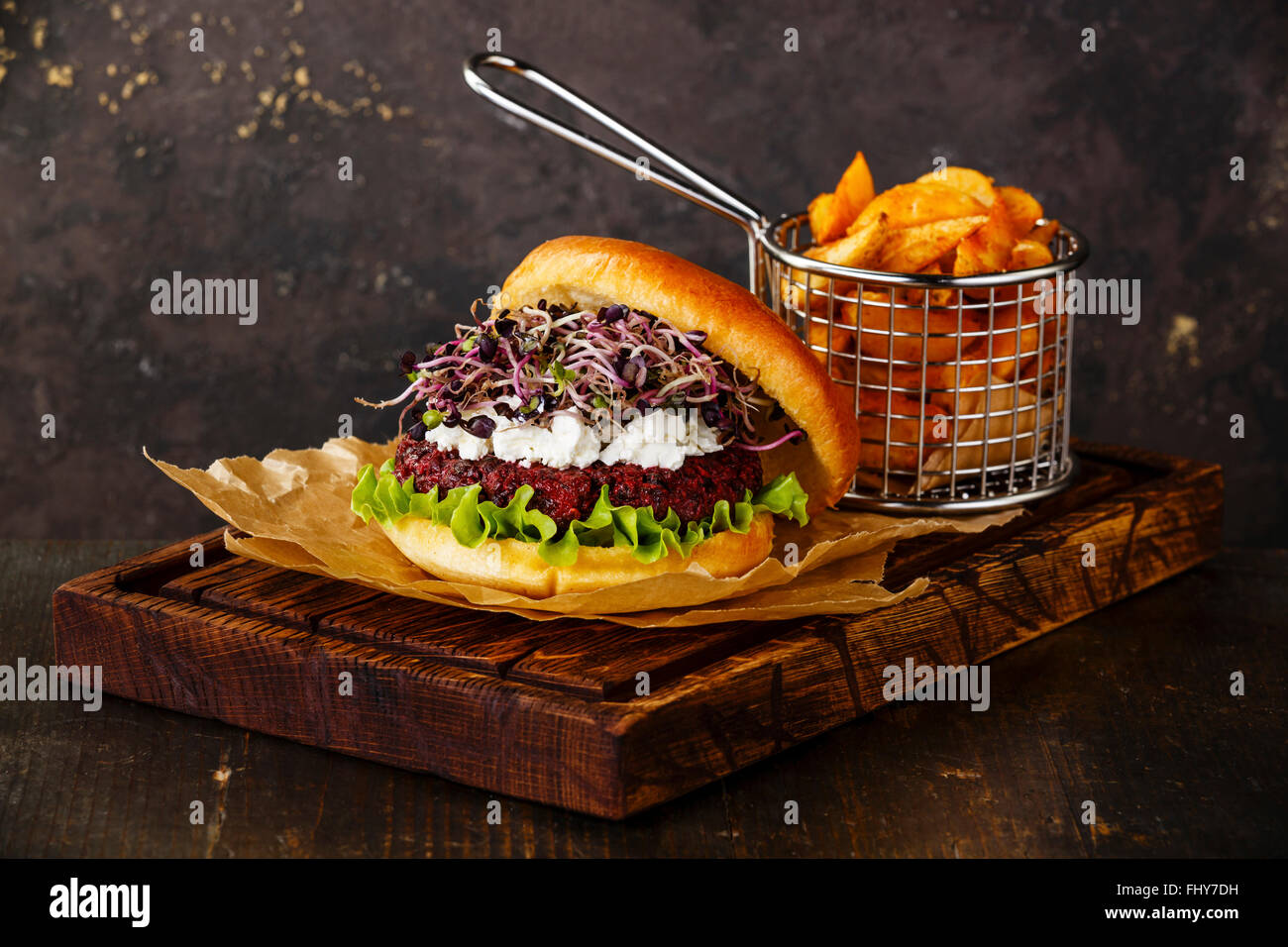 Beet burger with soft cheese radish sprouts and potato wedges on dark background - Stock Image