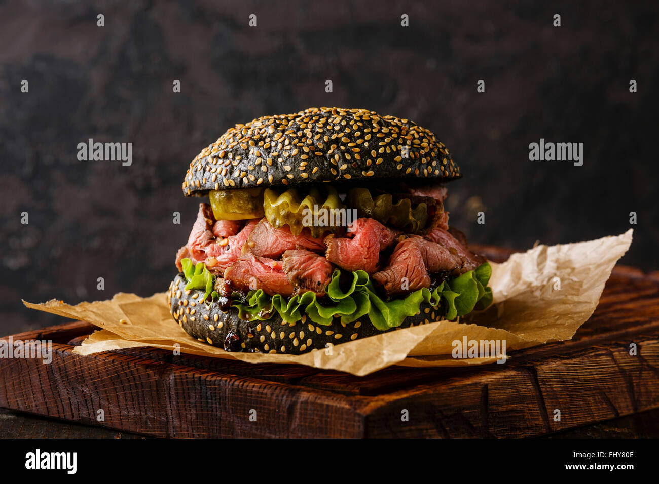 Roast beef Burger Takeaway snack on sesame bun with sliced Pastrami and pickle on black background - Stock Image