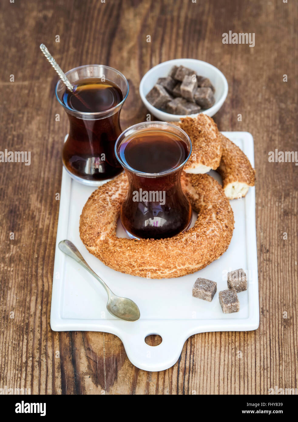 Turkish traditional black tea in a glass and turkish bagel simit on white ceramic serving board over wooden background - Stock Image