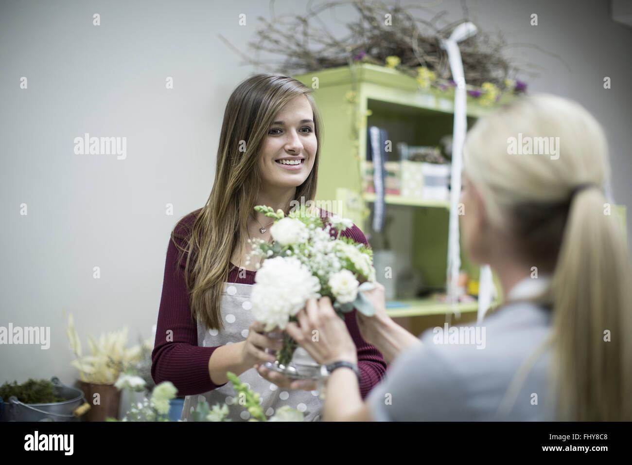 Smiling florist in flower shop presenting flower arrangement - Stock Image