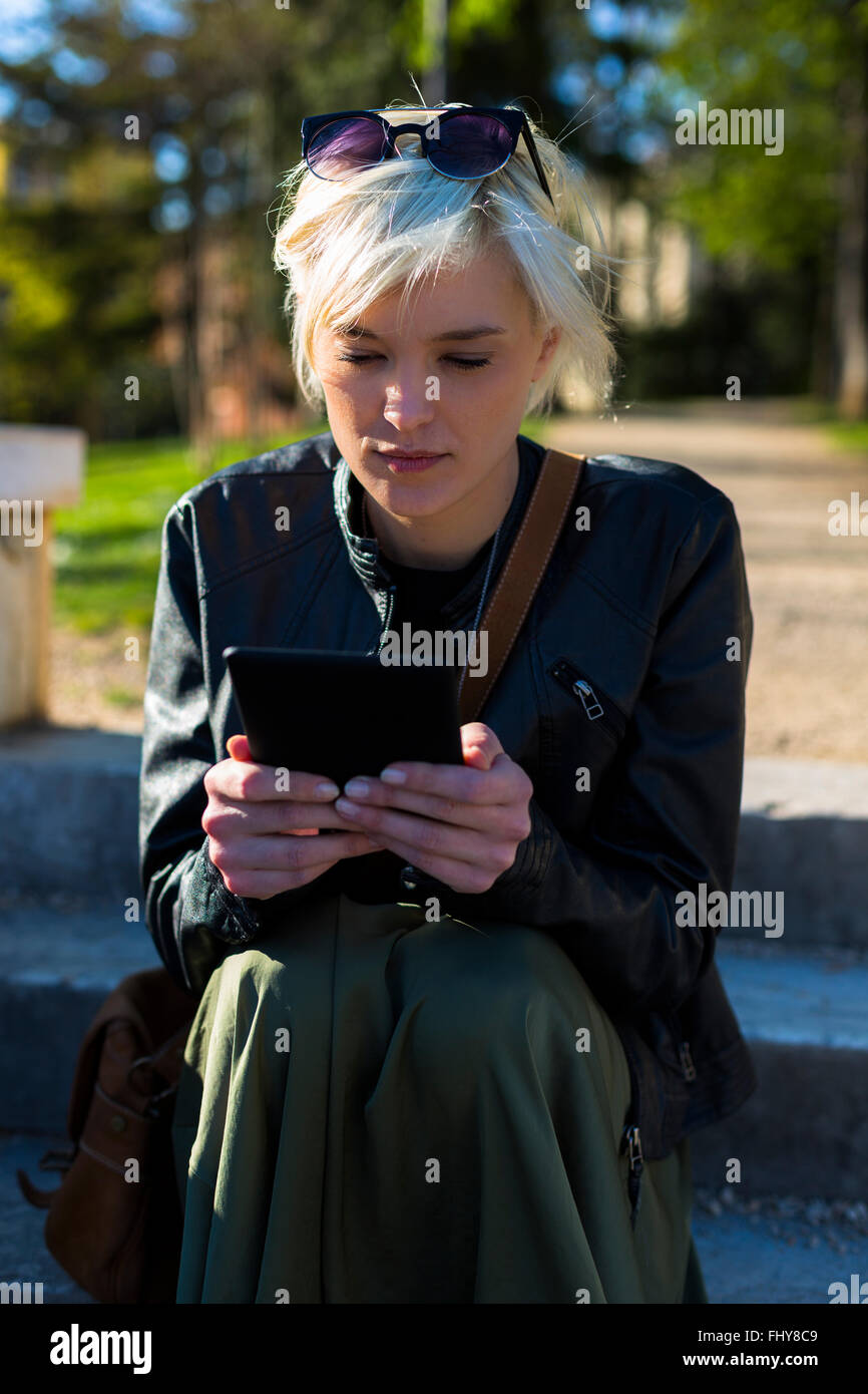 Portrait of blond woman reading an ebook - Stock Image