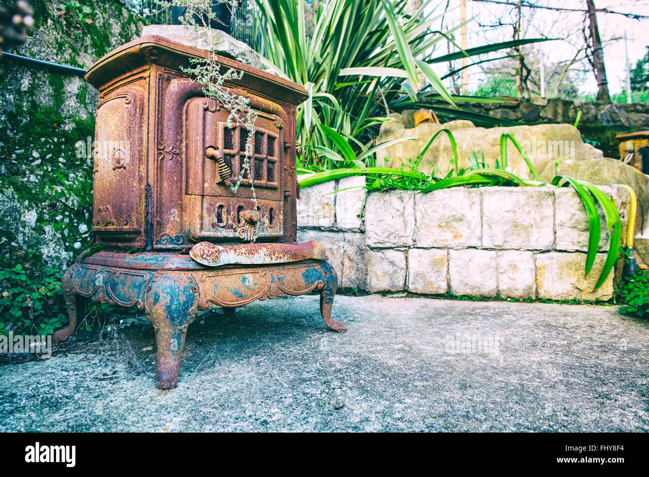 old fireplace in the garden whit flowers - Stock Image
