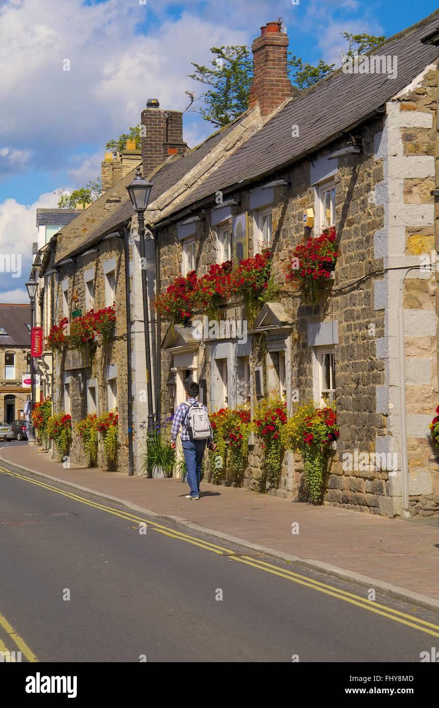 Man walking with ruck sack. The Black Bull Pub, Corbridge, Northumberland, England, United Kingdom, Europe. - Stock Image