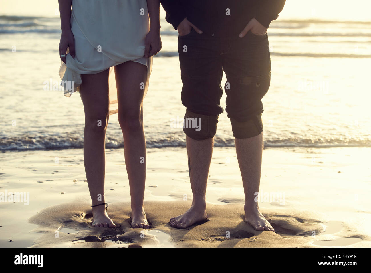 Spain, Cadiz, legs of young couple standing barefoot atseafront - Stock Image