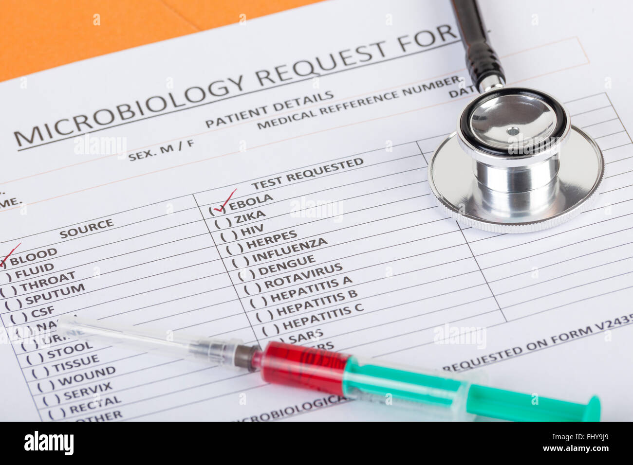 Microbiological blood test form showing a positive test result for the Ebola virus on a doctors desk with a stethoscope - Stock Image