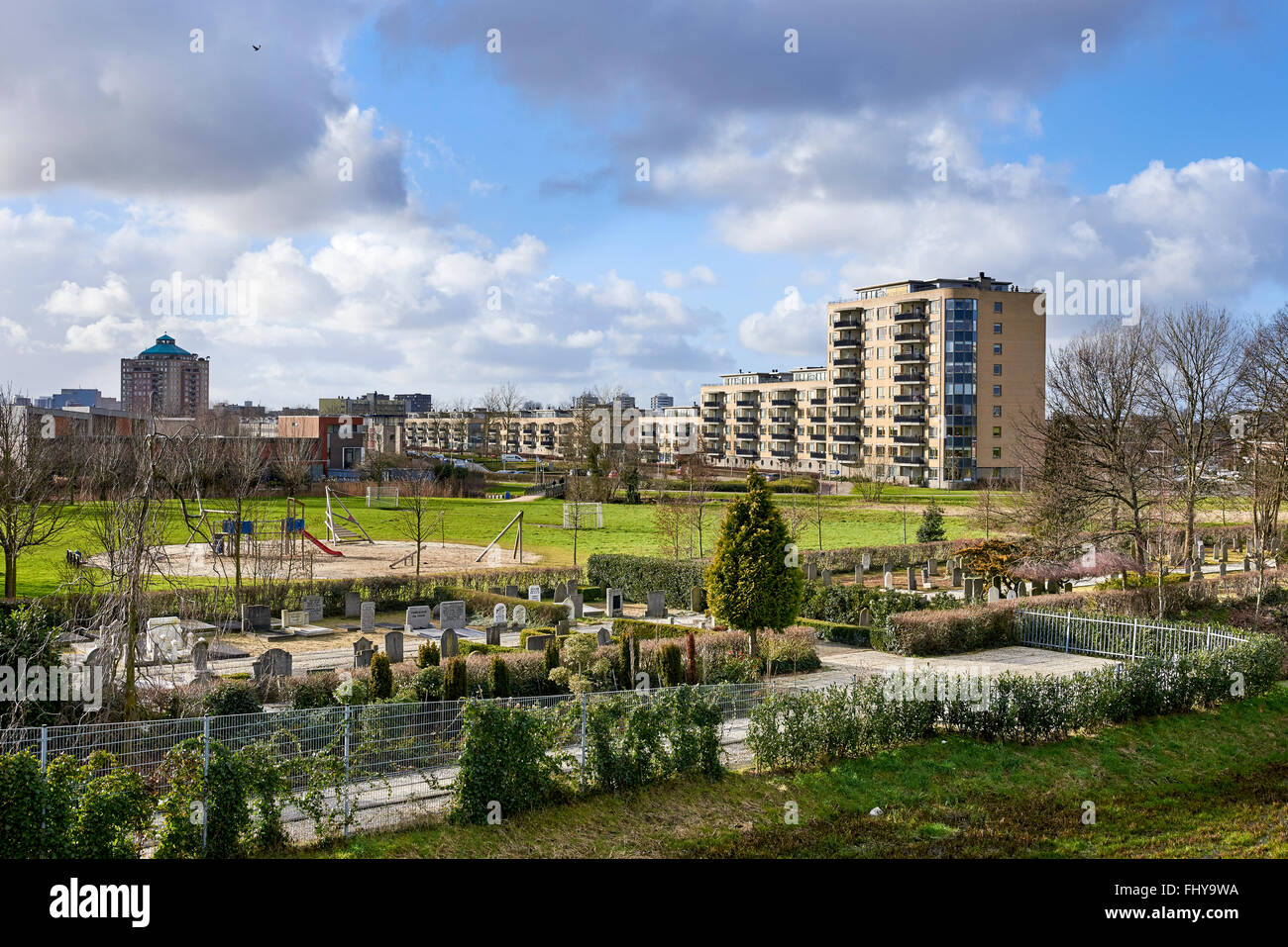 Graveyard, playground and apartment buildings. - Stock Image