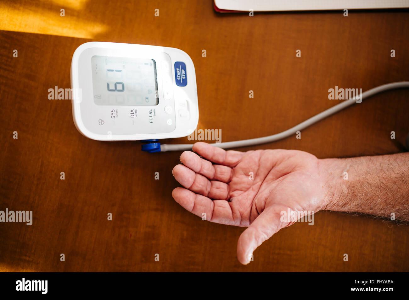 Hand of senior man using blood pressure gauge, close-up - Stock Image