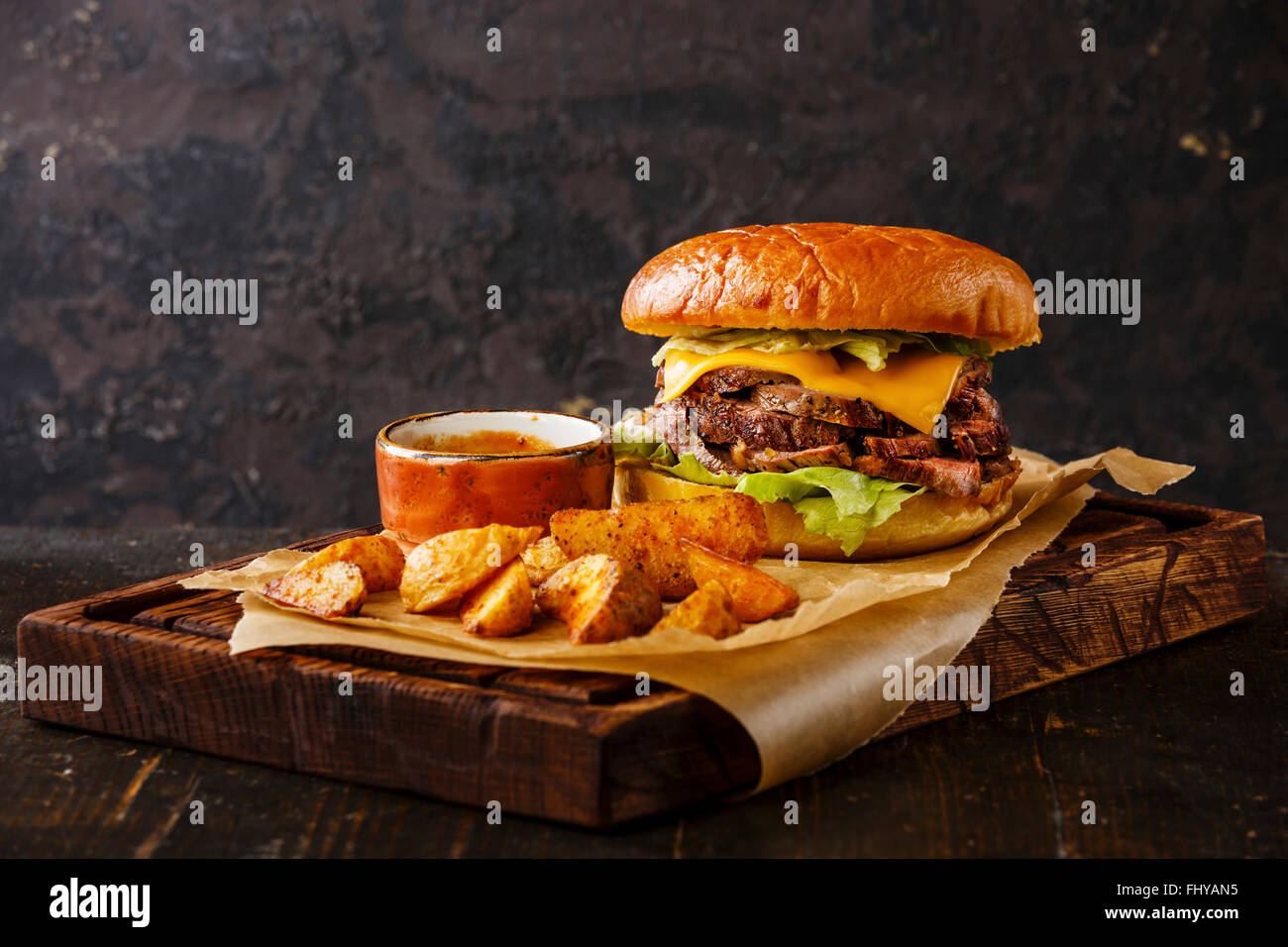 Pastrami Burger Takeaway snack with sliced Roast beef and potato wedges on dark background - Stock Image