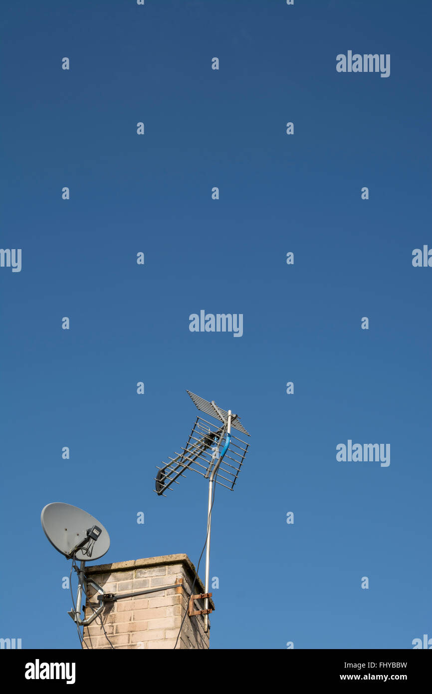 Digital TV aerial and satellite dish on a chimney against a blue sky. - Stock Image