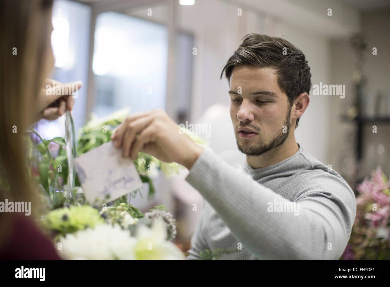 Man putting greeting card in flower arrangement - Stock Image