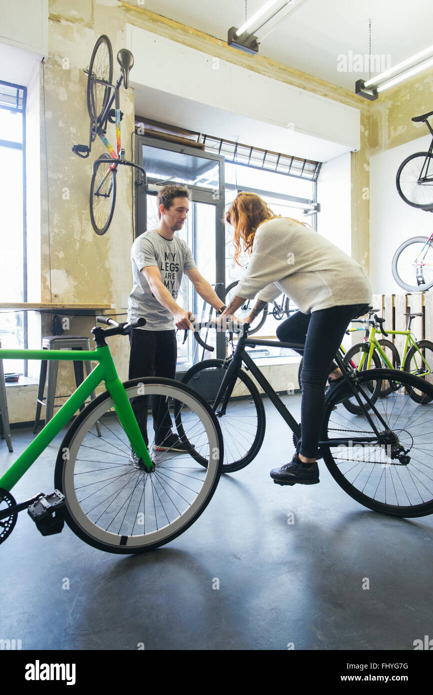 Client testing racing cycle in a custom-made bicycle store - Stock Image