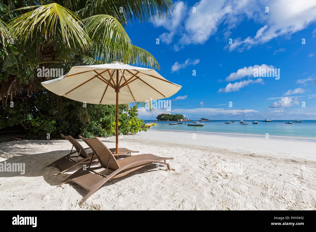 Seychelles, Praslin, Anse Volbert, Chauve Souris Island and Saint Pierre, beach with sun loungers Stock Photo
