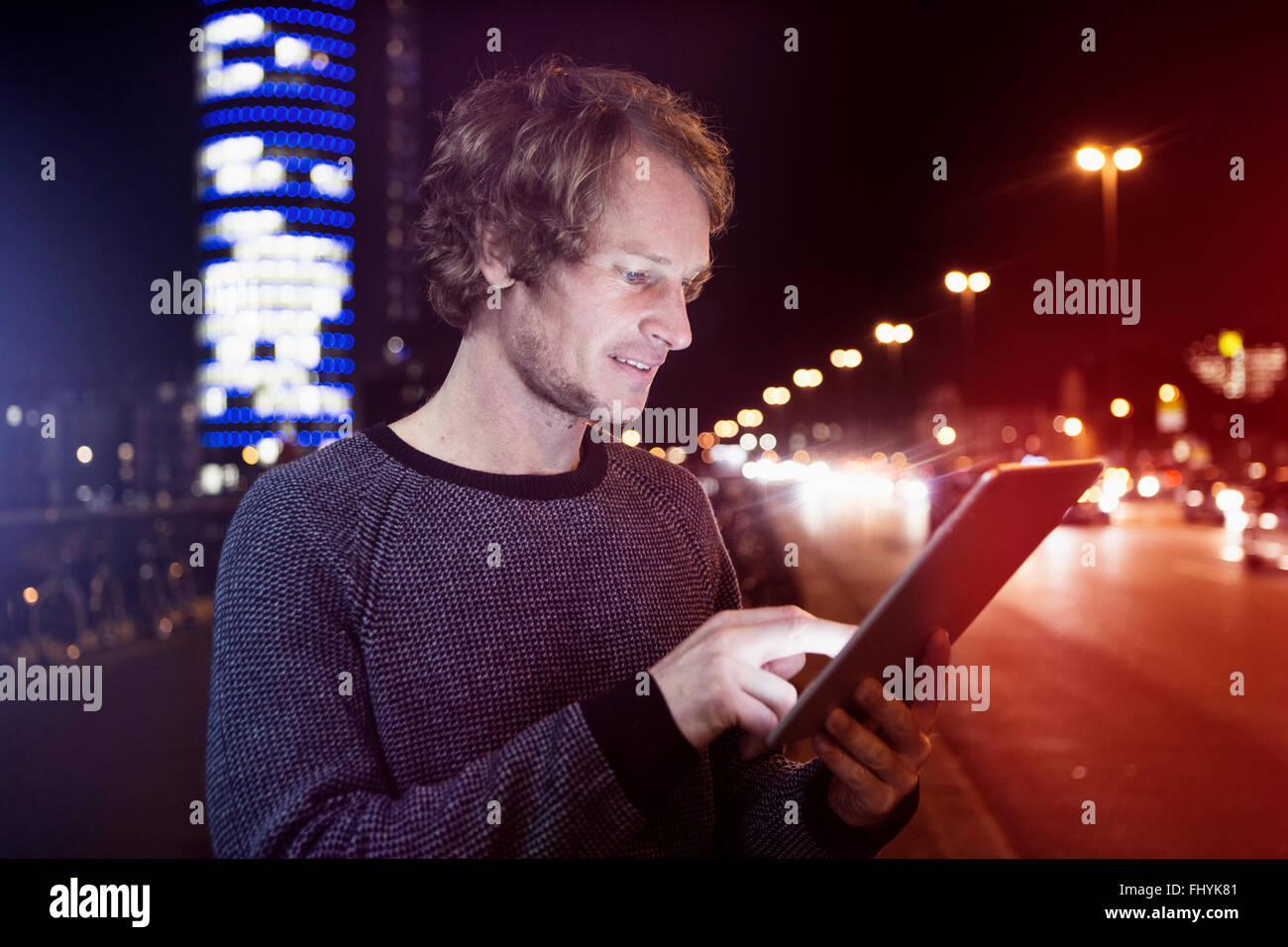Germany, Munich, portrait of man using digital tablet at night - Stock Image