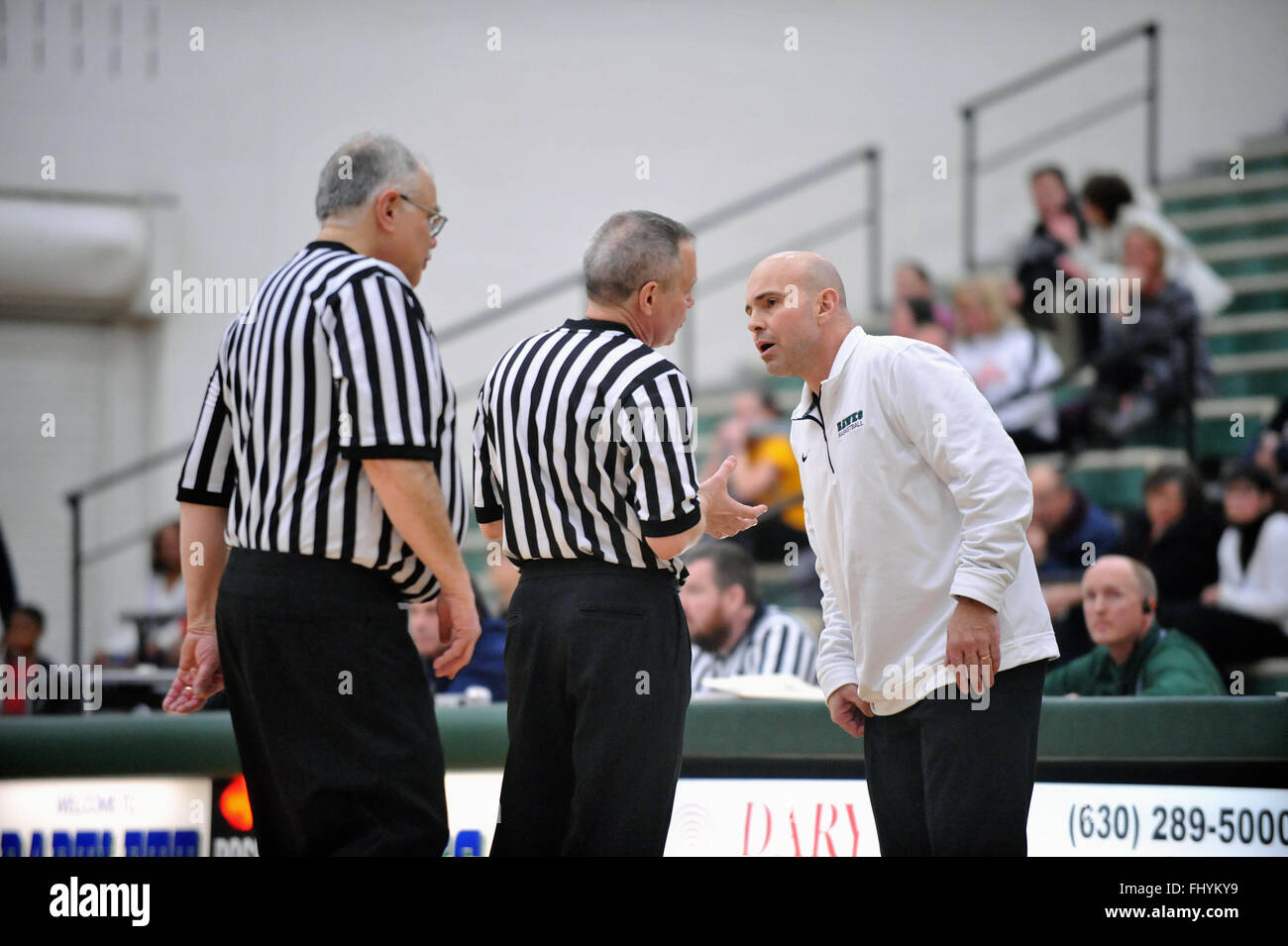 Following a call that he did not agree with, a high school basketball coach leans in to obtain an explanation from - Stock Image
