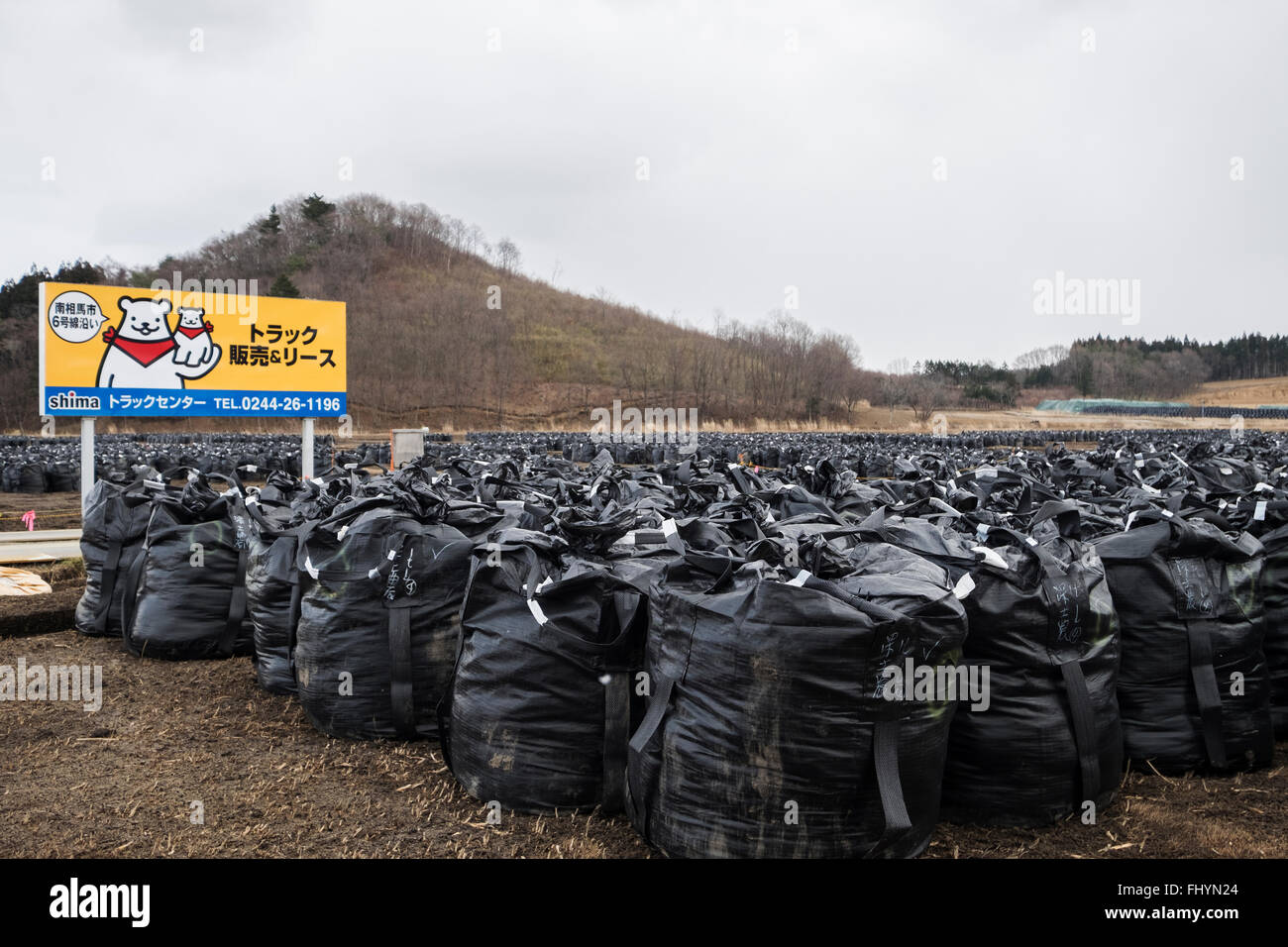 A sign adverting trucks is situated in a field with bags containing irradiated debris in Litate, Fukushima, Japan - Stock Image
