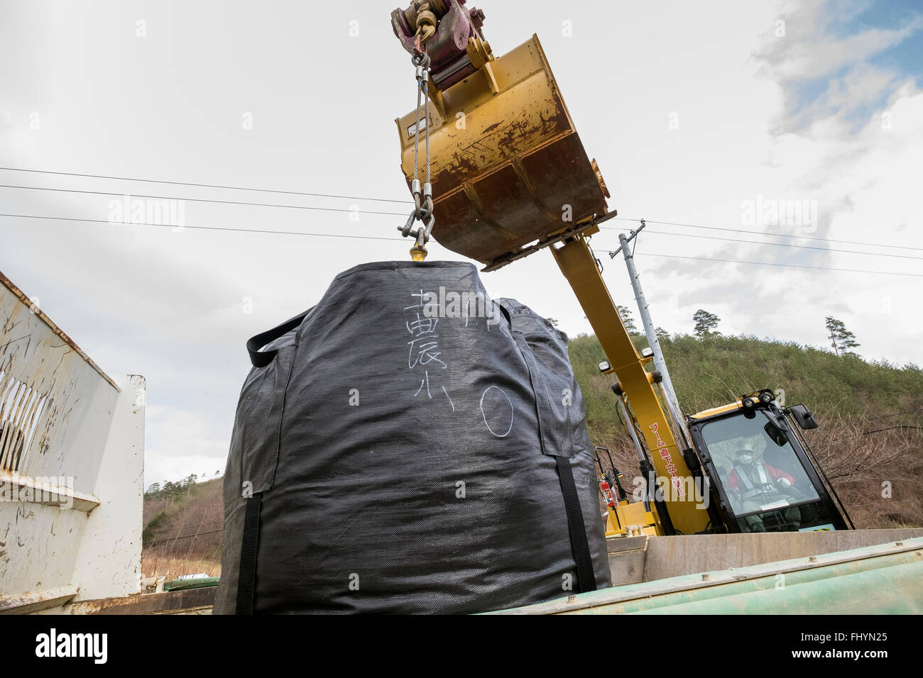 A bag containing irradiated debris is stacked on a truck in an area that was affected by the 2011 tsunami and nuclear - Stock Image