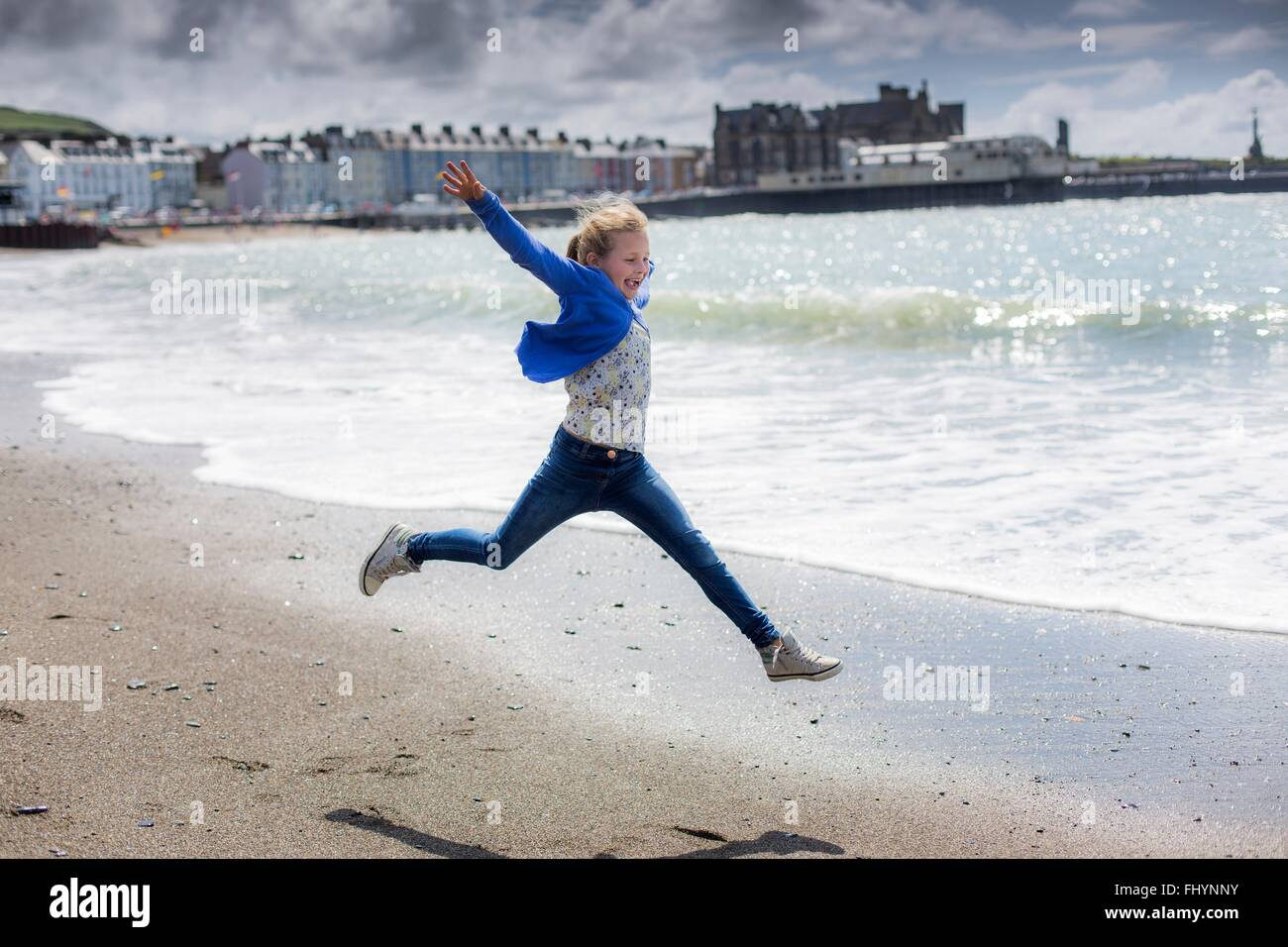MODEL RELEASED. Girl leaping on the beach. - Stock Image