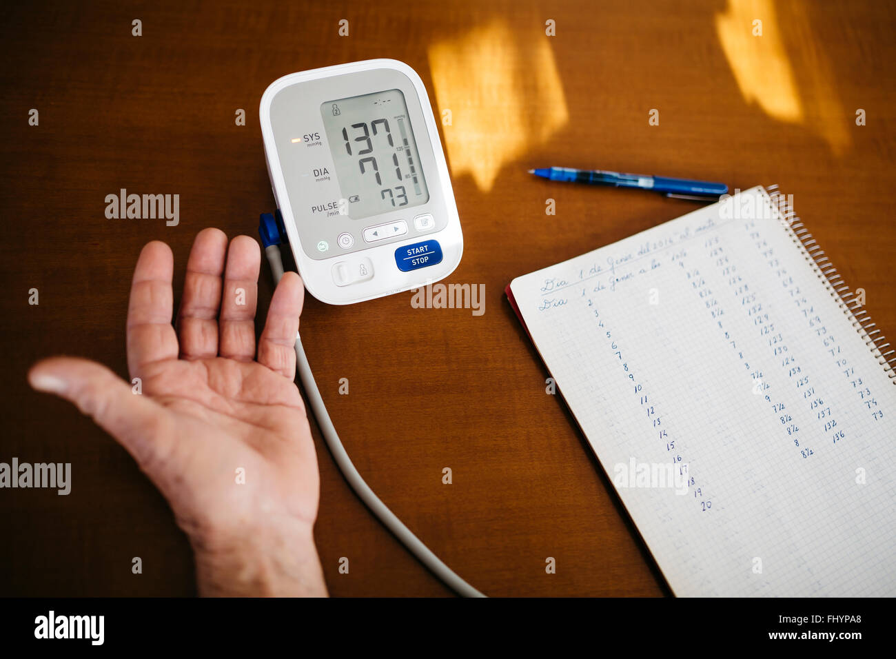 Hand of senior man controlling his blood pressure, close-up - Stock Image