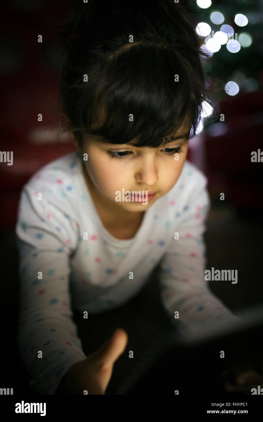 Portrait of little girl using digital tablet at home - Stock Image