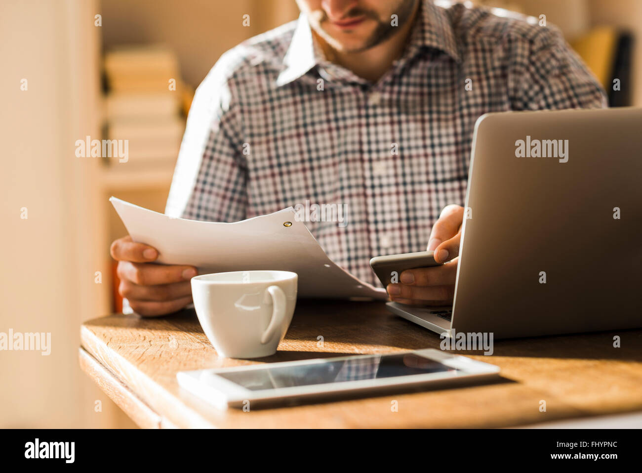 Man with document and mobile devices at desk - Stock Image