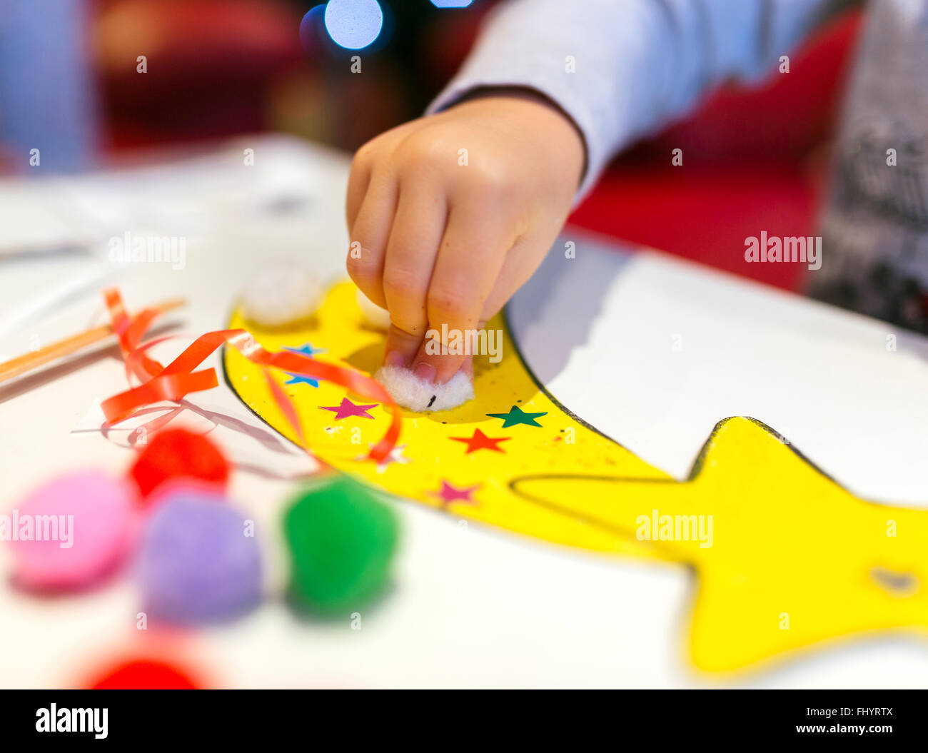 Hand of little girl tinkering Christmas decoration, close-up - Stock Image