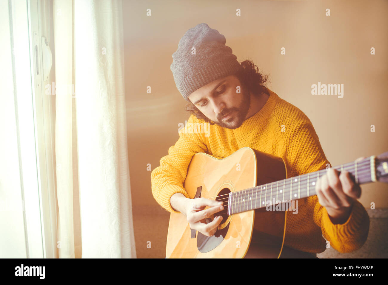 Man playing a acoustic guitar - Stock Image
