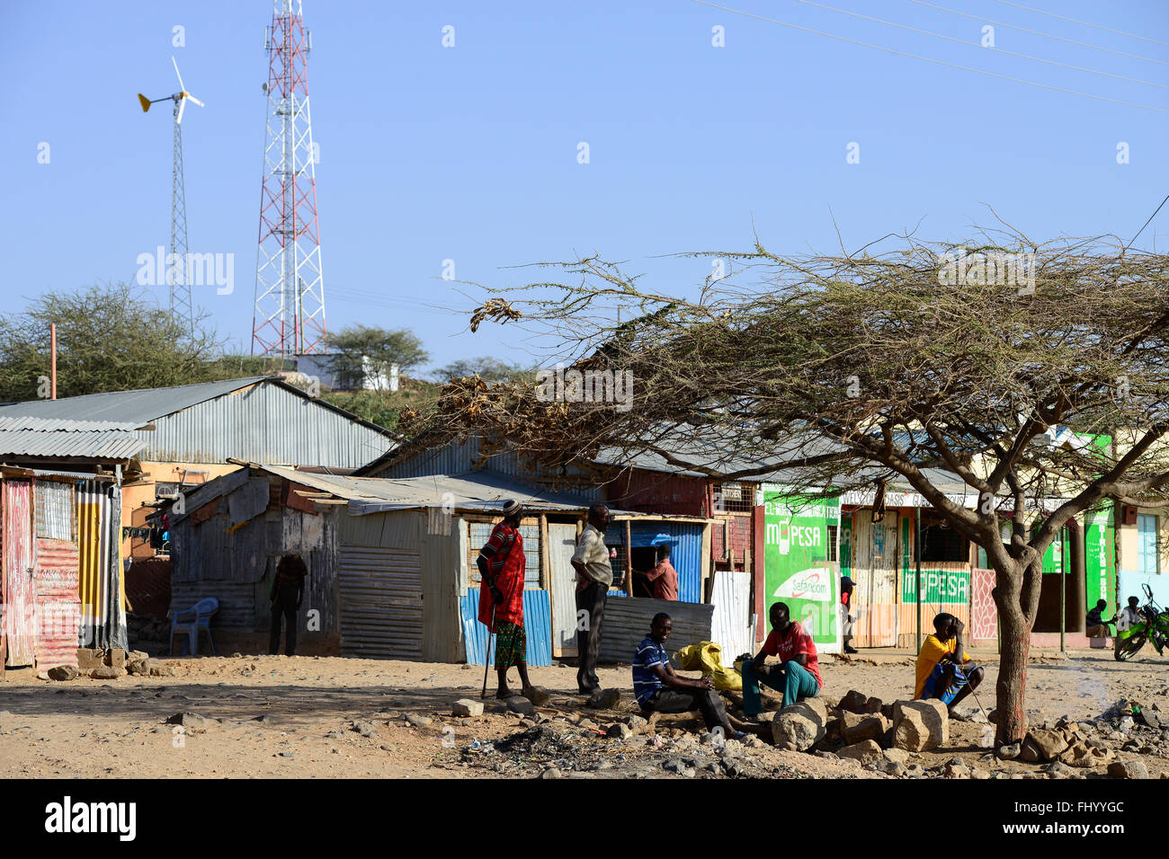 KENYA, Marsabit, village with lattice tower for mobile phone transmission and small windturbine, youngster infront - Stock Image