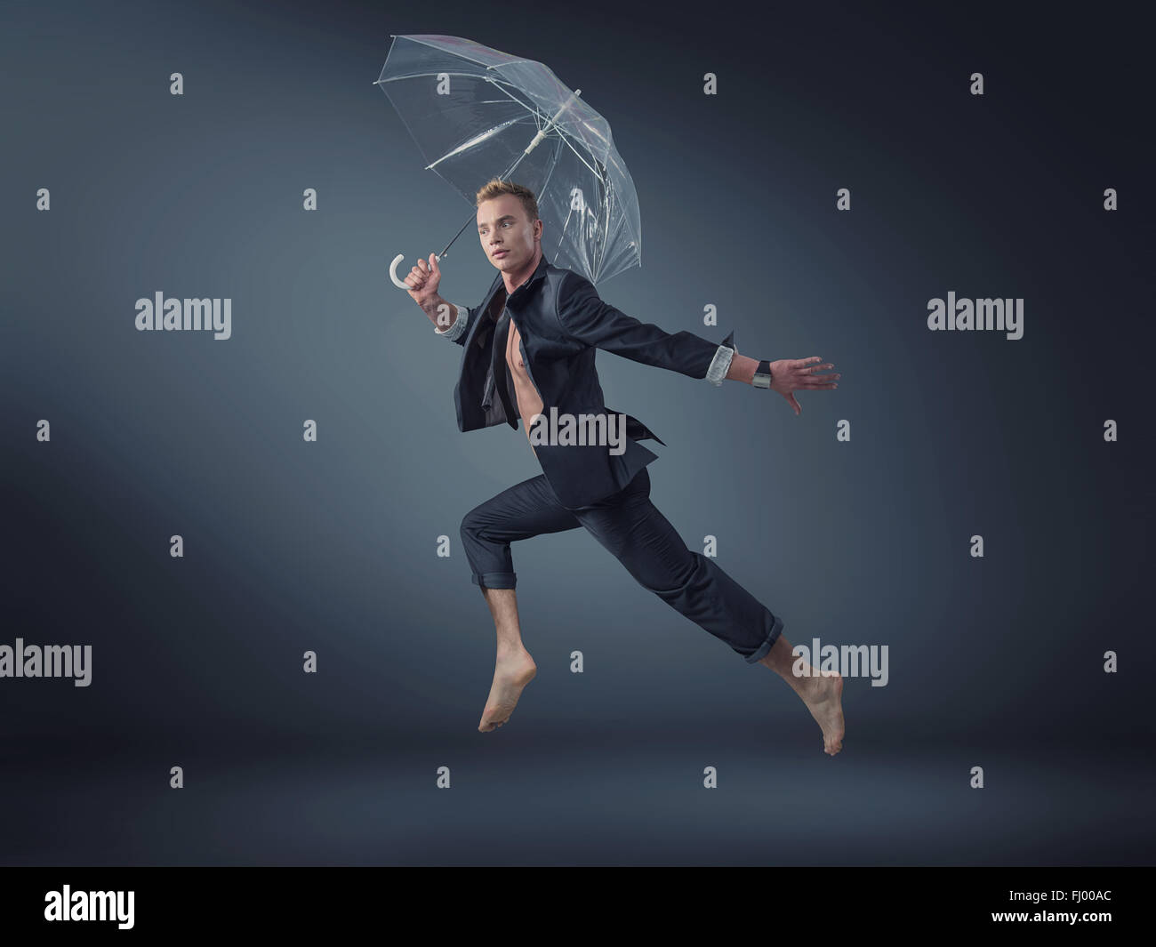 Handsome manager jumping with a transparent umbrella - Stock Image