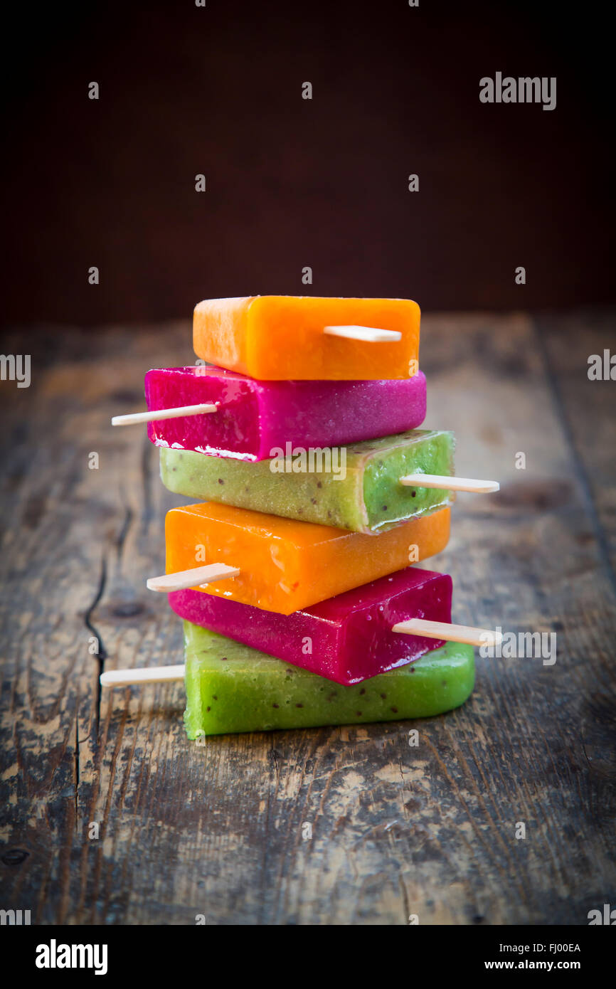 Stack of fruit smoothie ice lollies on dark wood - Stock Image