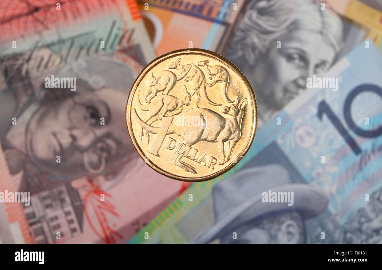 An Australian one dollar coin suspended over three bank notes. - Stock Image