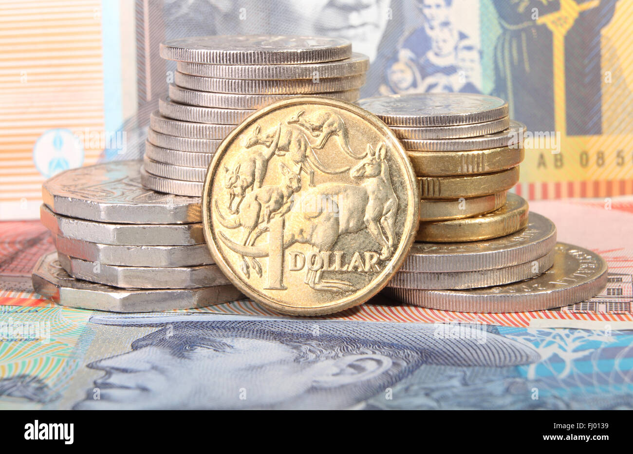 An Australian gold one dollar coin sits next to a stack of coins on top of Australian bank notes. - Stock Image